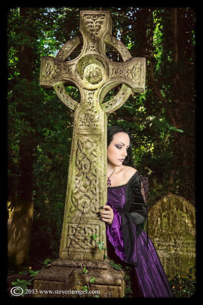 Celtic cross, Lady Amaranth, model in purple dress, graveyard, grave stones., photo