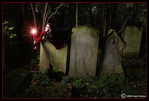 Model in long red dress with hood, Tower Hamlet cementery, photo