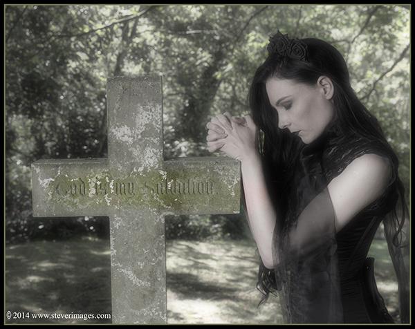 Cross, woman in black in prayer