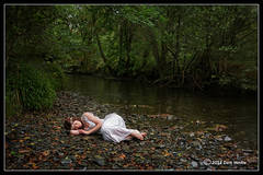 Woman in white, asleep, by riverbank