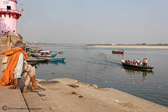 Man, sitting by river, Ganges, Varanasi, India