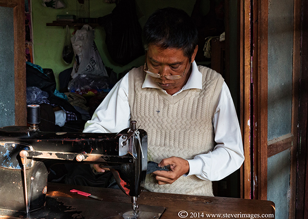 There were a number of people working at the back of the market sowing and making/reparing garments, both men and women.