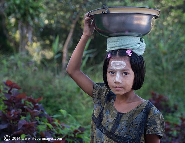 child carrying bowl on head, Yangon, photo