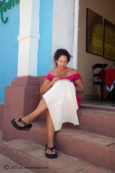 Knitting, Trinidad, Cuba, Image of person seating on steps and knitting in Trinidad, Cuba.