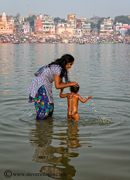 Bathing baby in the river, river Ganges, Varanasi, India, photo