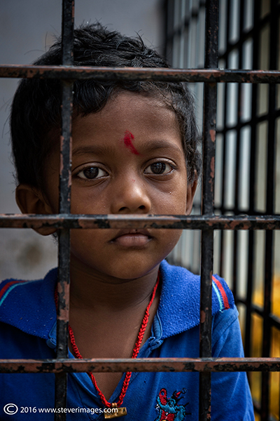 Indian boy in blue, behind bars, photo
