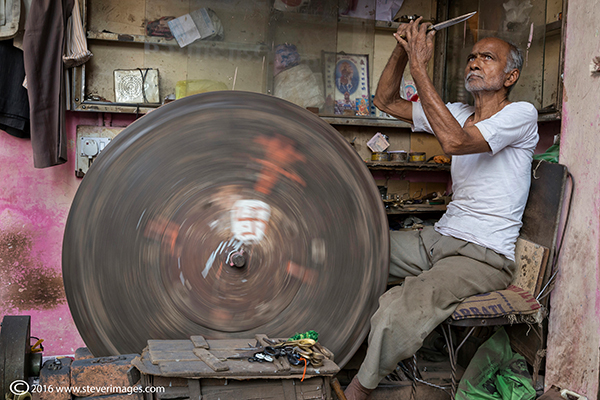 Indian man sharpening knife, photo