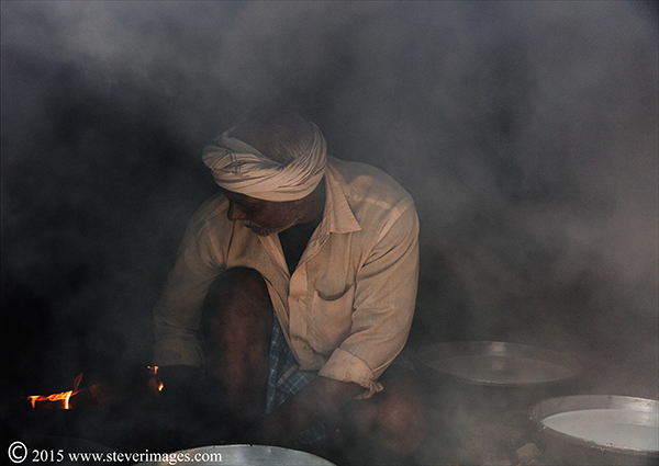 Indian workman with smoke and fire , back streets of Varanasi, India, photo