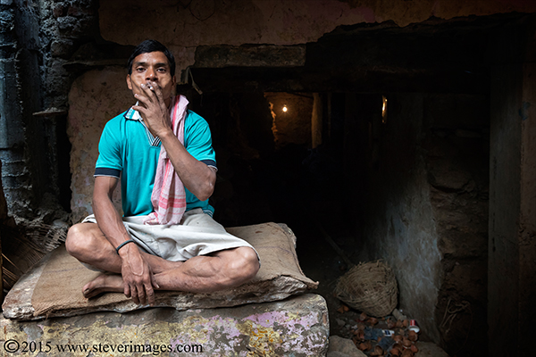 man smoking, back streets Varanasi India, photo