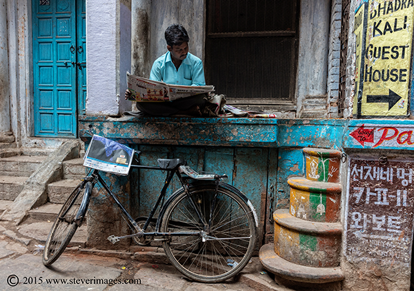 man reading paper, back streets of Varanasi, photo