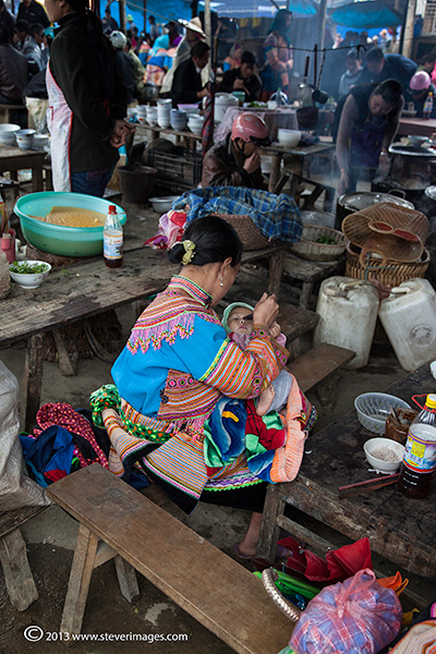 Mother feeding child, Bac Ha market, North Vietnam, photo