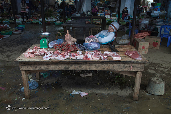 Person asleep at market stall,Bac Ha market North Vietnam , photo